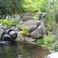 ручей , впадающий в крупны садовый водоем